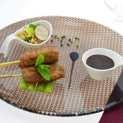 Kefta d'agneau croustillant parfumé à la menthe et tomate, bâtonnets de céleris braisés au poivre vert et pétales d'ail noir