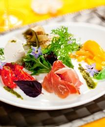 Salade printanière aux légumes confits, chèvre  frais, pesto, jambon seché, roquette, fleurs de bourrache et vinaigre balsamique