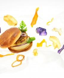 Burger de poisson, confit d'oignons, crème au raifort et pousses d'épinards
