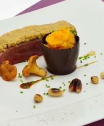 Filet de canette en croûte de fruits secs, timbale de chocolat noir farcie de potiron braisé, jus de viande aux girolles